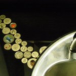 Women's restroom/washroom sink counter with embedded coins