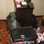 Suitcase and bag in the only space of the room, view from entrance door to the 'fridge