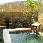 新緑の木立の庭に露天風呂が