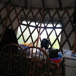 Back side of Yurt has kitchen table with 4 chairs and a bench.