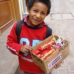 Young boy selling chocolates outside hotel