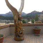 A cool statue on the patio by one outdoor pool
