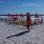 Beach scene showing lifeguard chairs and a surfer coming back in.