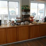 Cafe Room is a cozy dining area w/ granola bars, chips, pastries, cookies, yogurt, water, and co
