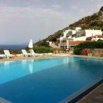 Het zwembad van Adrakos appartments met daarachter de appartementen.