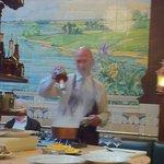 Waiter preparing sauce