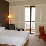 In dem Zimmer stehen 2 Betten. Es hat einen kleinen Balkon mit Blick  auf die Stadt