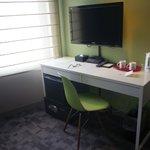 Стол с ТВ-панелью, справа электрочайник. Слева, под столом, холодильник.
