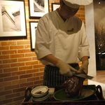 Preparing the Peking Duck by the table.