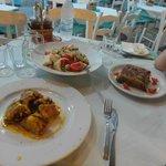 Salade, gevuld varkensvlees met saffraansaus, moussaka