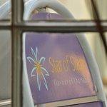 Star of Siam sign on sidewalk through window