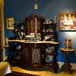 The full view of the ornately carved breakfront in the dining room with a painting next to it.