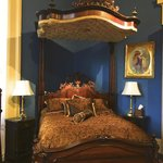 The queen bed with very ornately carved headboard, footboard, sideboards and canopy.