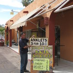 Owner Santiago in front of shop sign