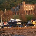 View from Watermouth Cove back to castle and lodges in trees.