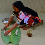 Tharu woman preparing traditional dish