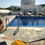 Breakfast of Greek yogurt and fresh peaches by the pool