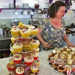 Jenine with cakes at official opening of the Olive Tree