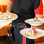 Die freundliche nette Bedienung serviert Pizza und Pasta-Gerichte.