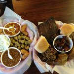 A BBQ sampler with ribs, brisket, pulled pork, dark chicken, Brunswick stew and some sides.
