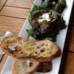 Grilled grape leaves stuffed with goat cheese and served with artisanal bread
