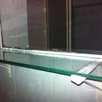 sharp edge on glass shelf in bathroom complete with rusty brackets