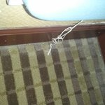 Corner below ironing board to right of entry door