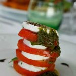 Tomato and mozzarella Napoleon with basil and red onion dressing.