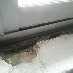 部屋の窓内側のボロボロのコンクリート