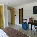Baño a la izquierda, espejo, tv, escritorio, puerta principal y entrada a la habitación contigua