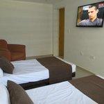 Vista de la habitación con dos camas, tv y silla (escritorio detrás)