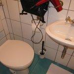 Beim sitzen auf Toilette, Bein unter Waschbecken