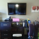 View from the bed, large tv, A safe and fridge built into cabinet, desk to right