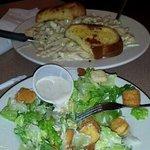 Half eaten caesar salad and chicken alfredo