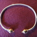 Silver bracelet with two gold balls