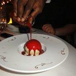 Waiter pouring hot rasperry sauce over the melting dessert, fantastic!