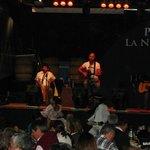 Adentro, los juglares en el escenario y dos bailarines debajo con trajes autóctonos