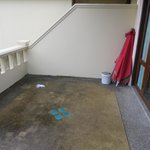Slippery, mouldy balcony used tissue paper, cement filled paint tin umbrella stand