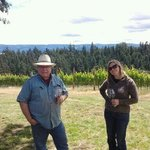 proprietor Bob sips wine in the vineyard with a guest