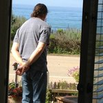 In the doorway of the cottage, you can see the ocean