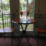 Table for two with beautiful flowers in background behind French doors