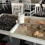 box frame tables filled with sand and shells