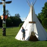 husband in front of tepee with rock floor, looks comfy