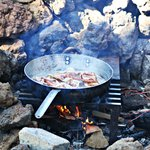 Bacon cooking in the firepit