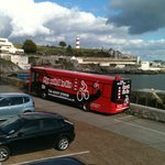 The Bike Bus and a moody sky over Plymouth Hoe.  Bikes ready for hire.