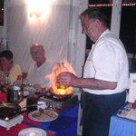 el cheff cocinando uno de sus platos flambeados en la mesa