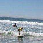 Criançada fazendo aula de surf