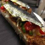 sardinas sobre piperrana y pan tostadito.