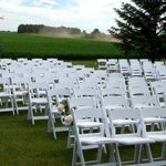 Chairs in front of alter, tent to left of chairs and wheat field at the back of the chairs.