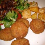 Delicious fried meatballs with salad and roasted potatoes.